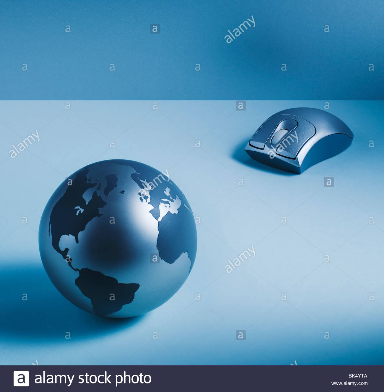 Metal globe and wireless computer mouse - Stock Image