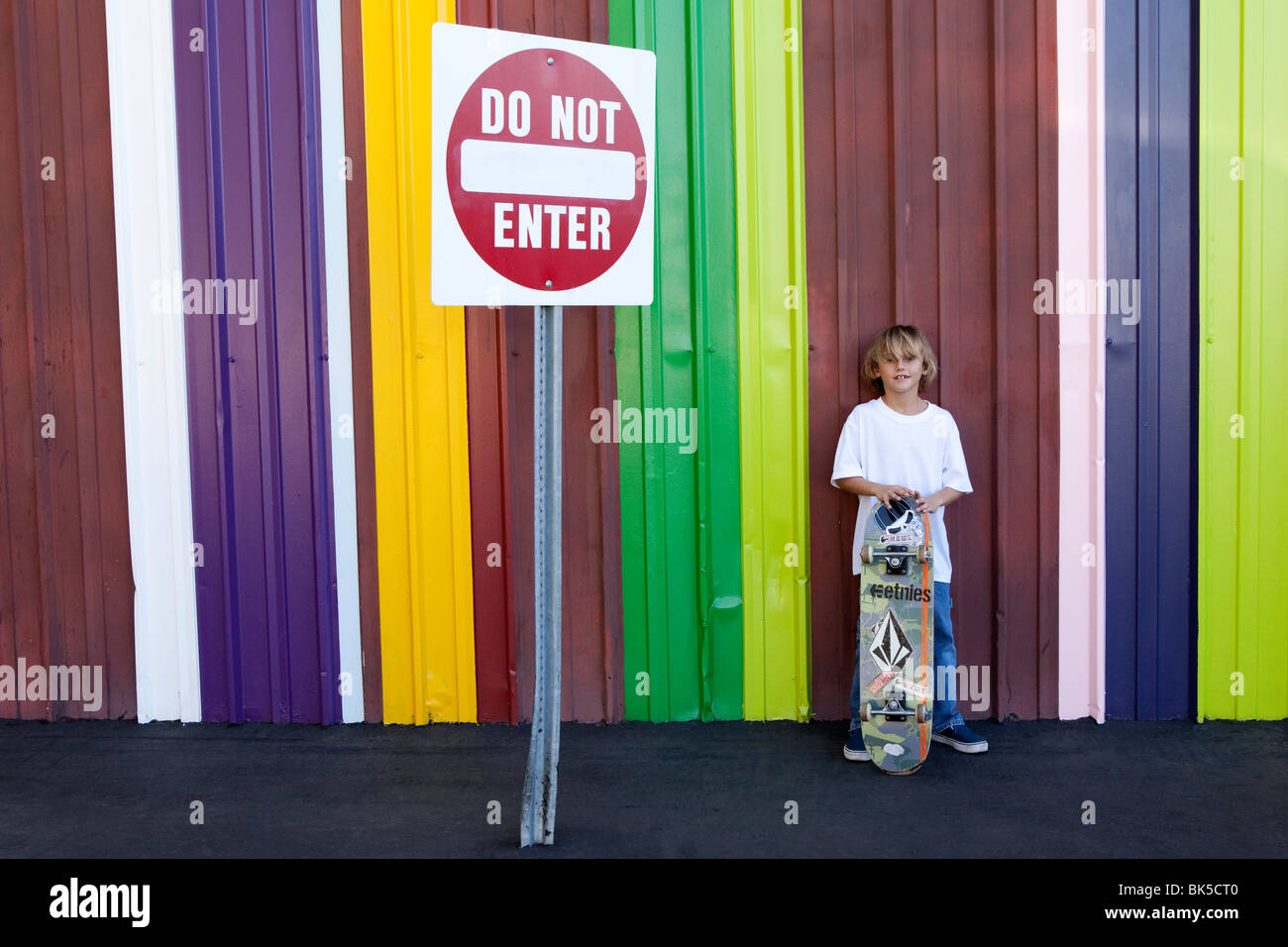 Boy with skateboard in front of colorful striped wall - Stock Image
