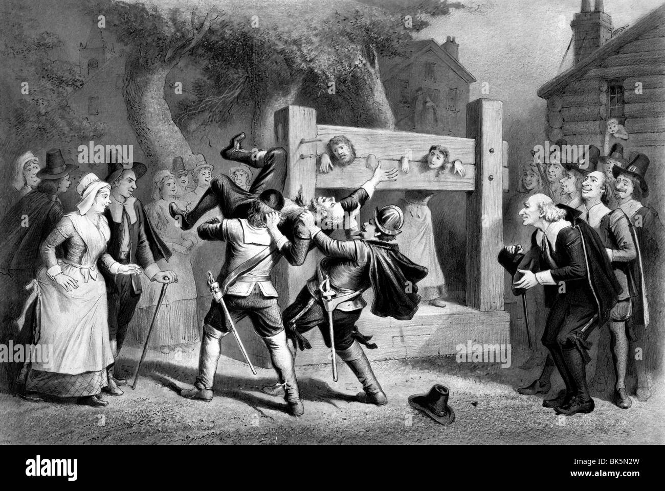 The witch, number 2. A hysterical scene in early New England with a man being dragged away and a couple in a pilloryStock Photo