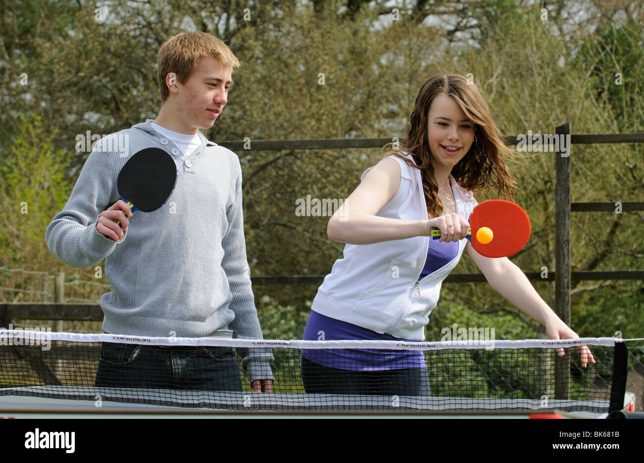 Teenagers playing a game of table tennis in their garden - Stock Image