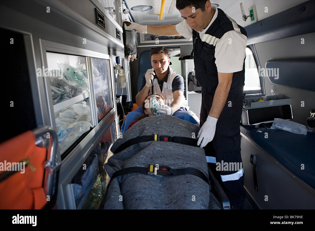 Ambulance staff and patient on stretcher - Stock Image