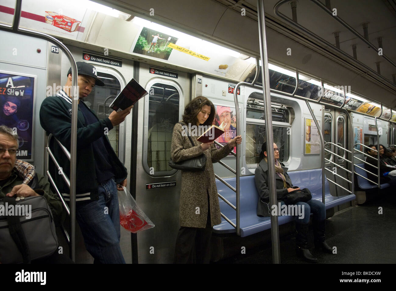 Commuters, standing, reading books on the subway in New York, on Sunday, April 18, 2010. (© Frances Roberts) - Stock Image