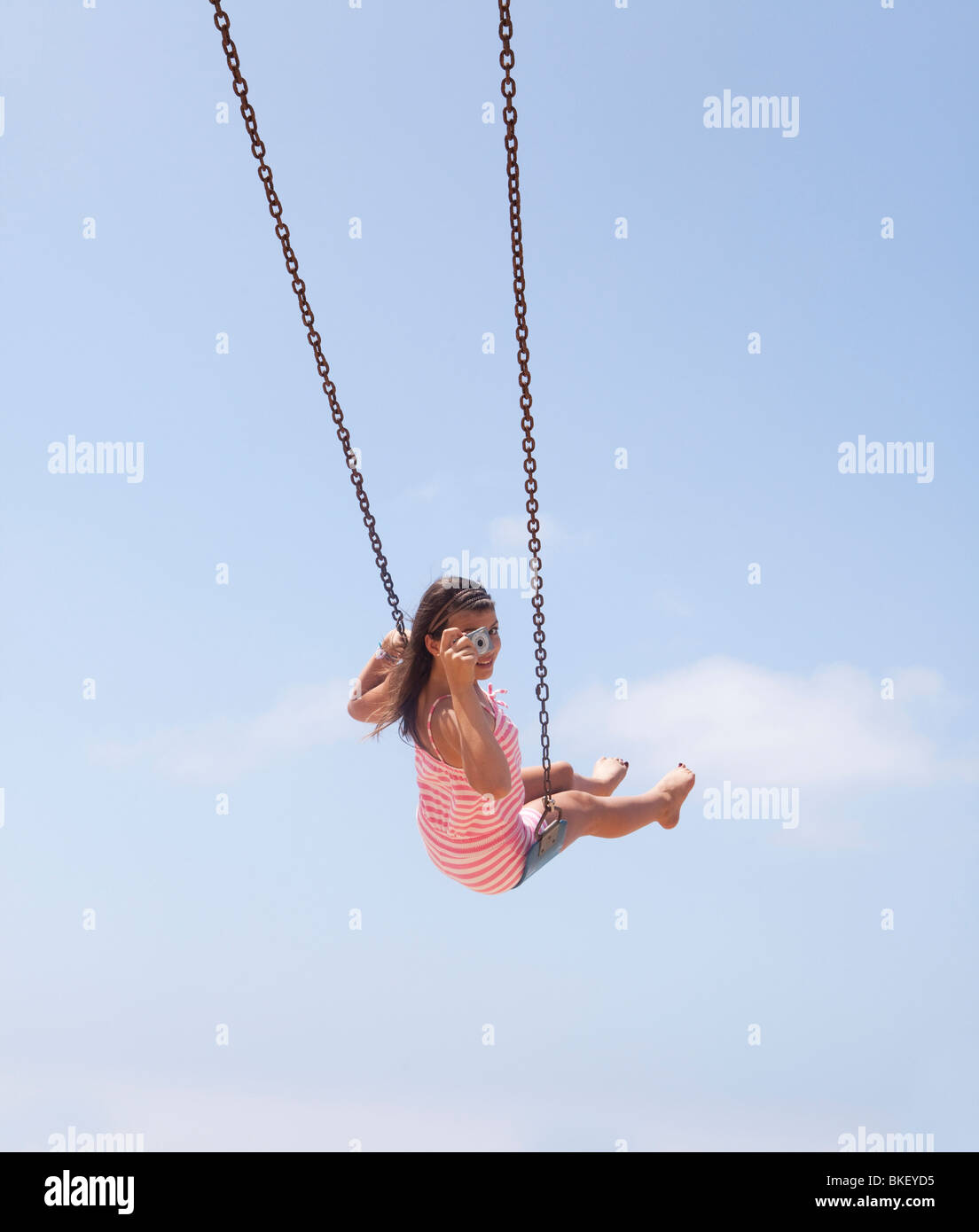 Girl taking picture from swing - Stock Image