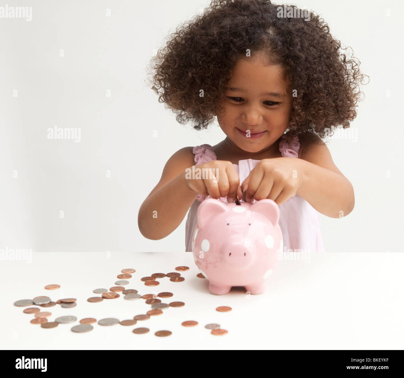 Young girl putting money in piggy bank - Stock Image