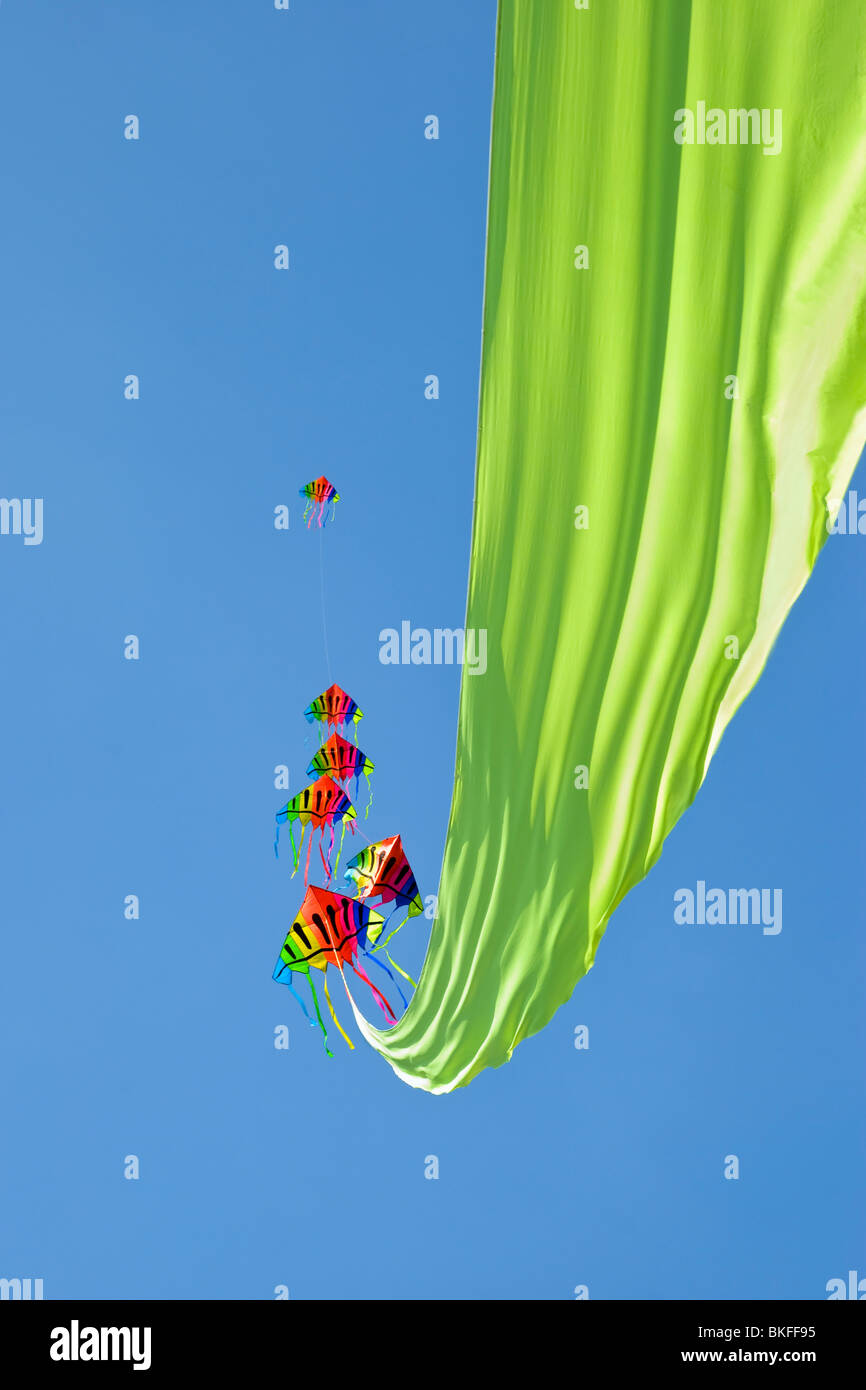 A very colourful kite with six heads and a long, lime green ribbon floating out behind it, taken at the Bristol - Stock Image