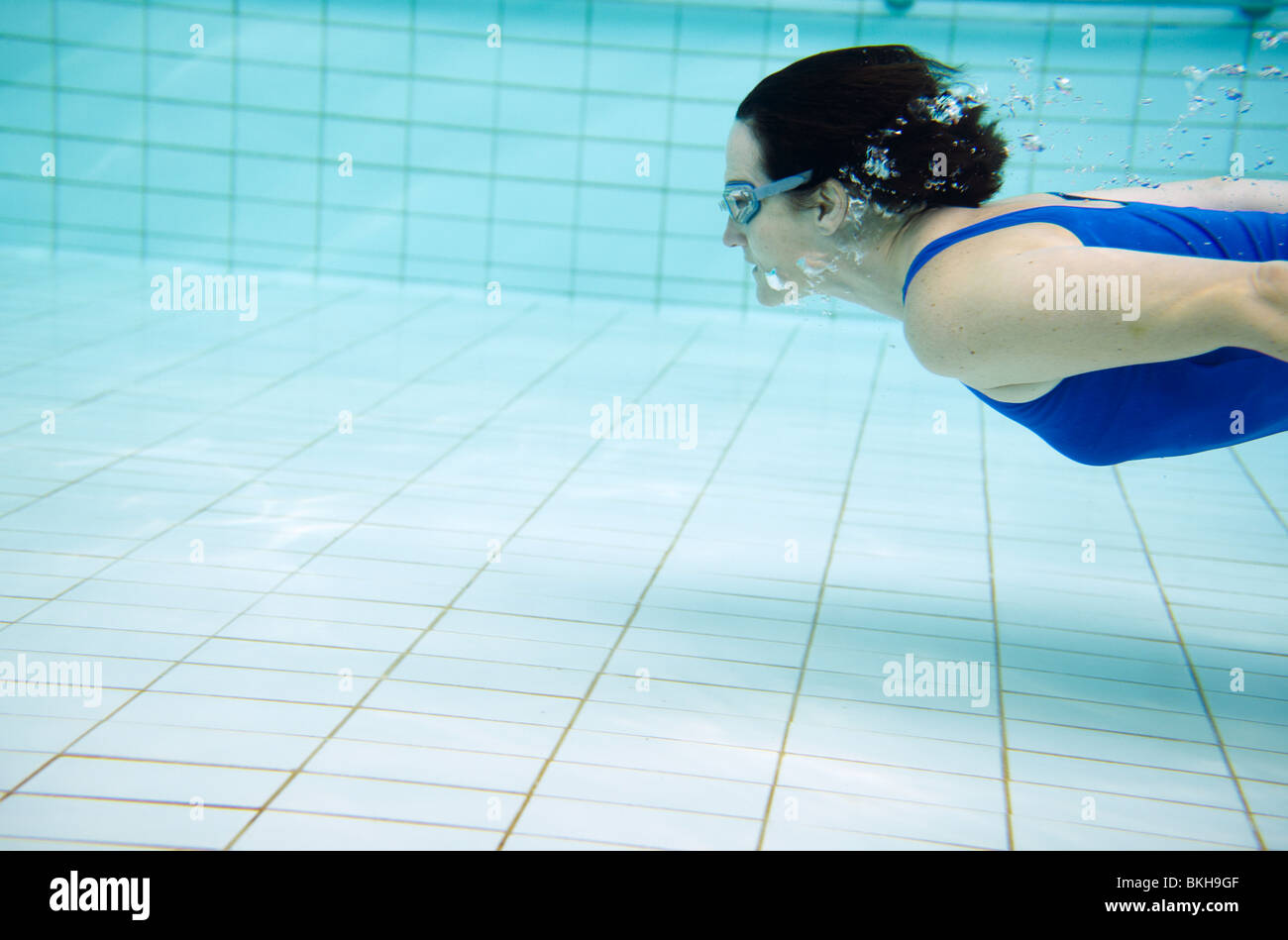Woman in blue swimming costume swimming under water in pool - Stock Image