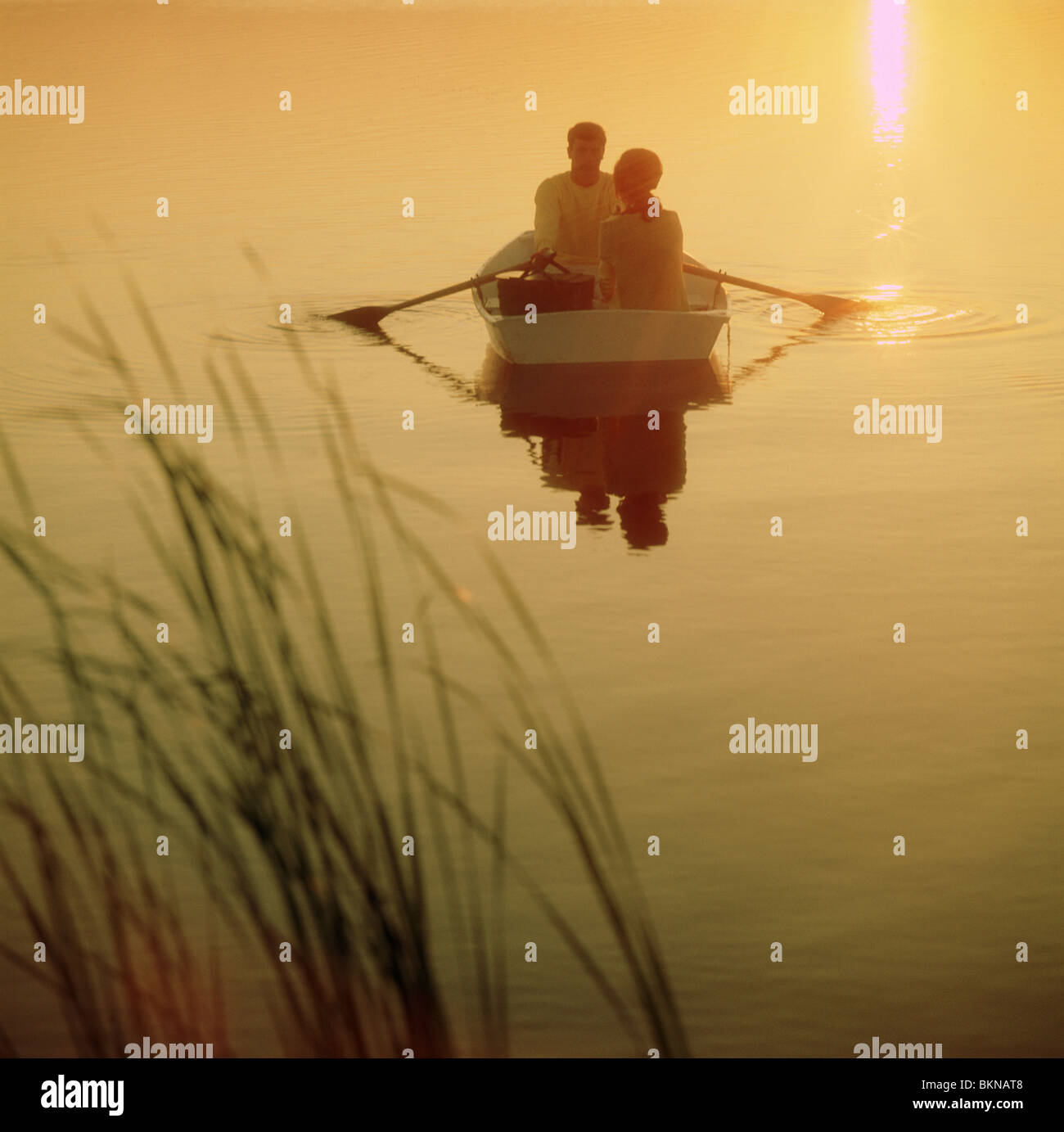 Couple on a row boat during the sunset Stock Photo