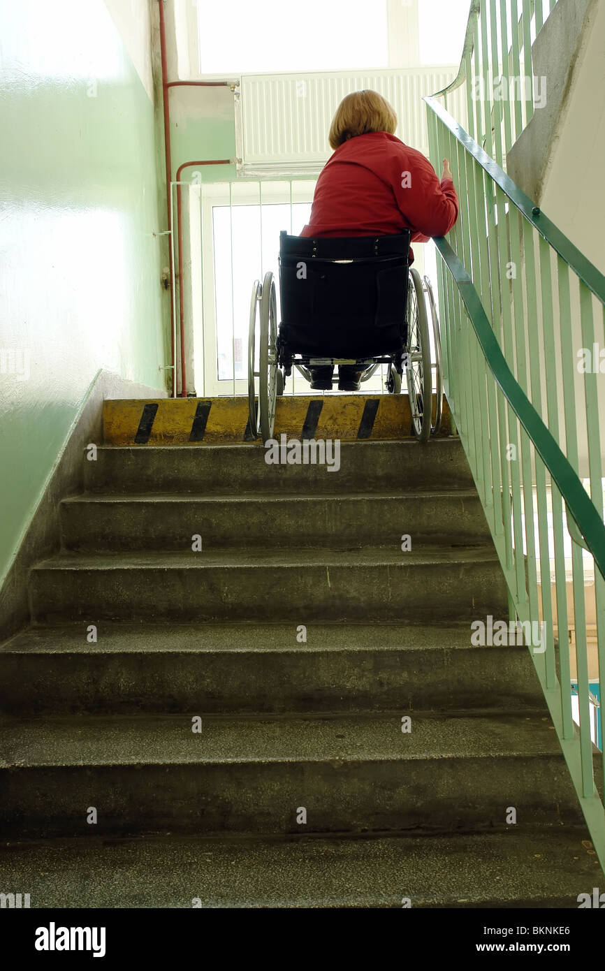 Handicapped woman on wheelchair going downstairs in building staircase - Stock Image
