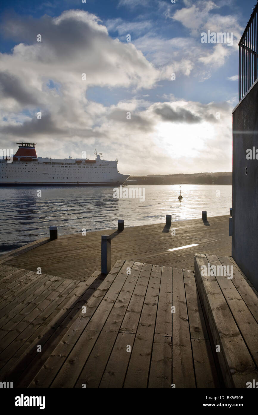 Jetty and passing ship - Stock Image