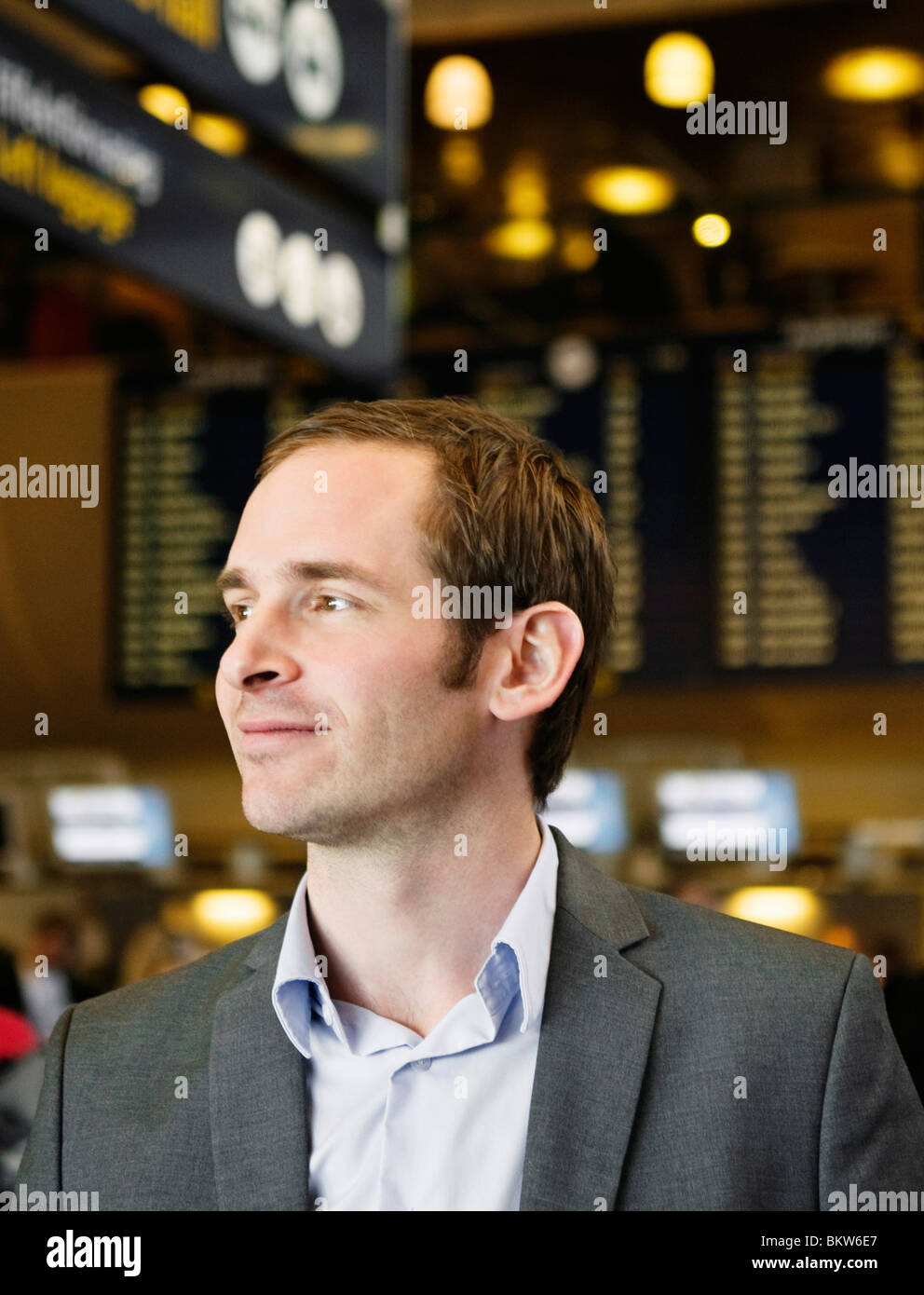 Man standing in departure hall - Stock Image