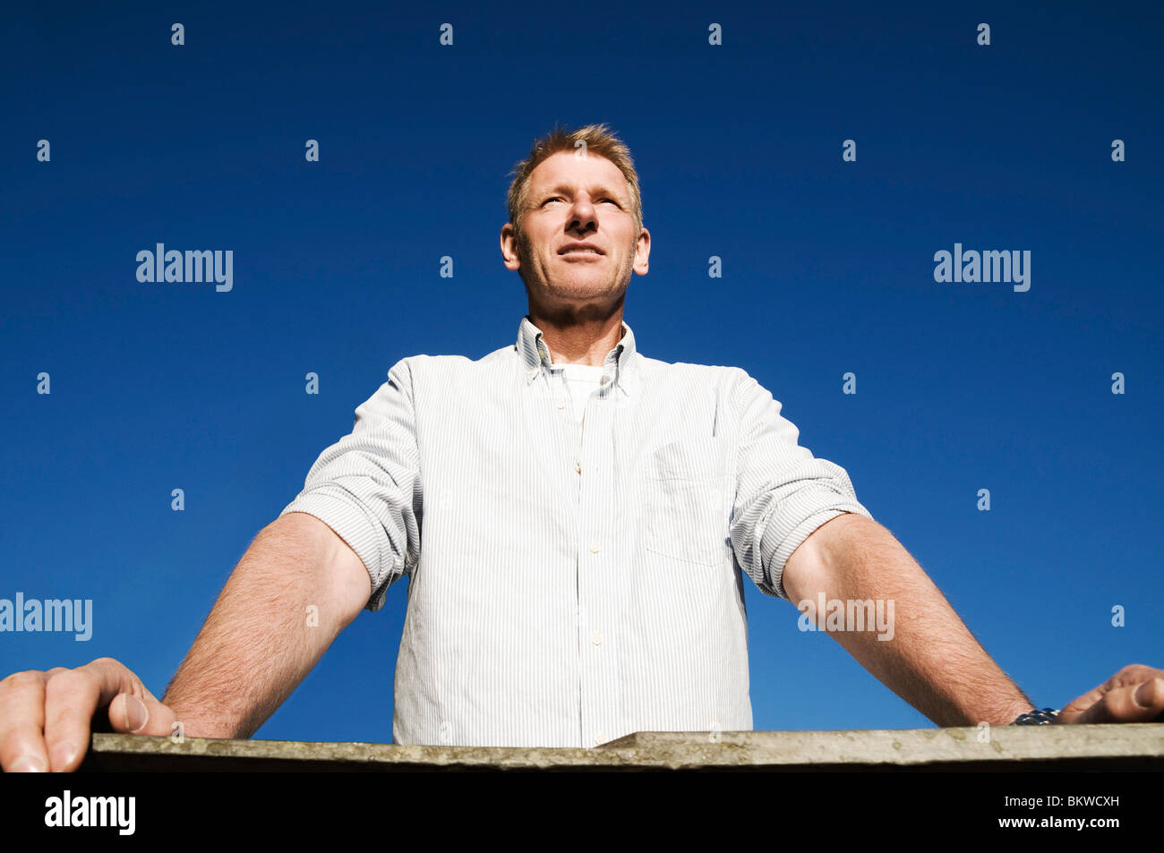 Man standing by rail - Stock Image