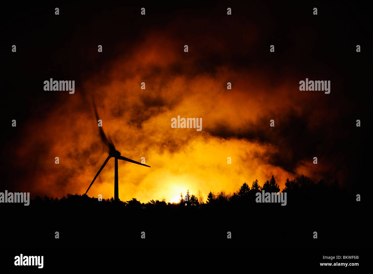 Wind power station against sunset - Stock Image