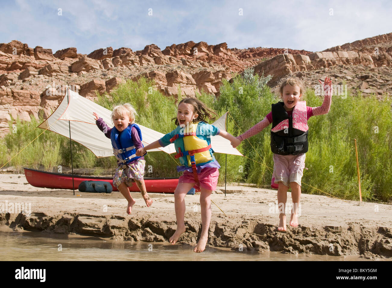 Three young girls in life jackets jumping into the San Juan River, Mexican Hat, Utah. - Stock Image
