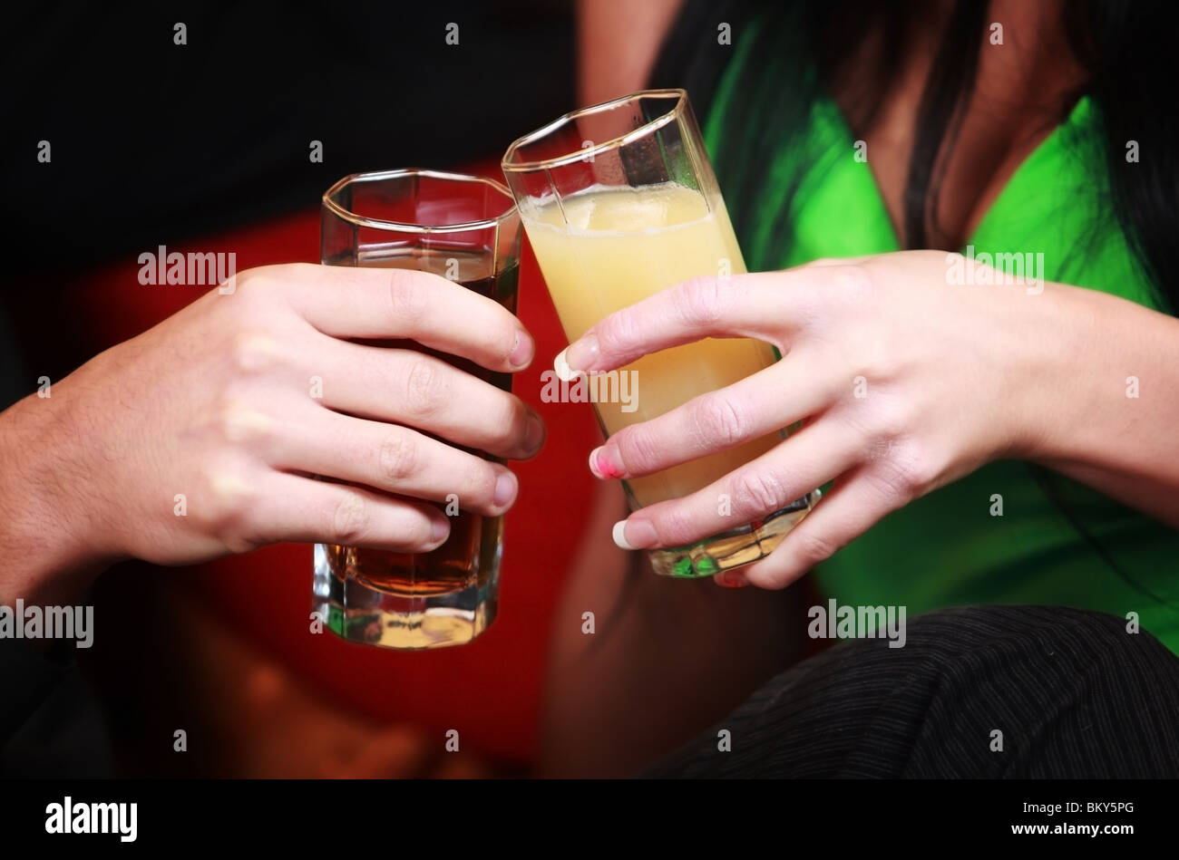 Close-up of two hands holding glasses with non-alcoholic drinks toasting - Stock Image