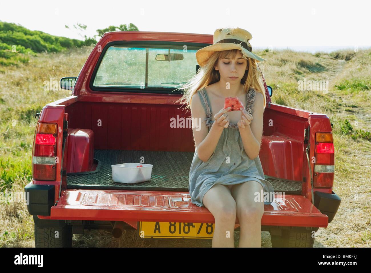 Girl eating watermelon on back of truck - Stock Image