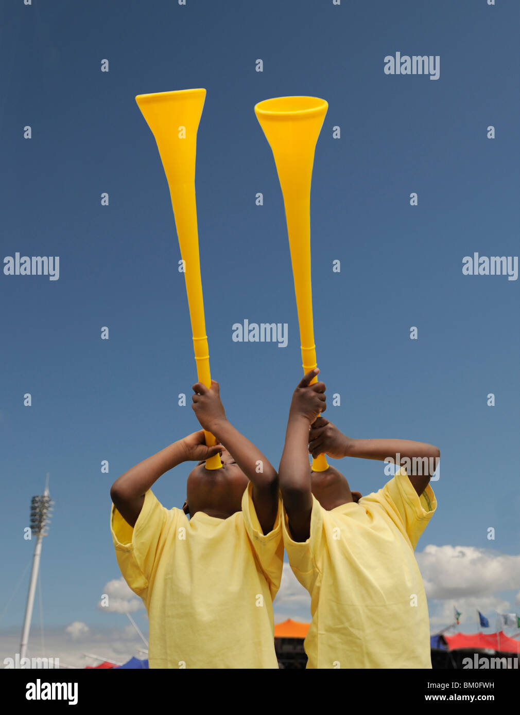 Two boys (2-3) with yellow vuvuzellas, Cape Town, Western Cape Province, South Africa - Stock Image