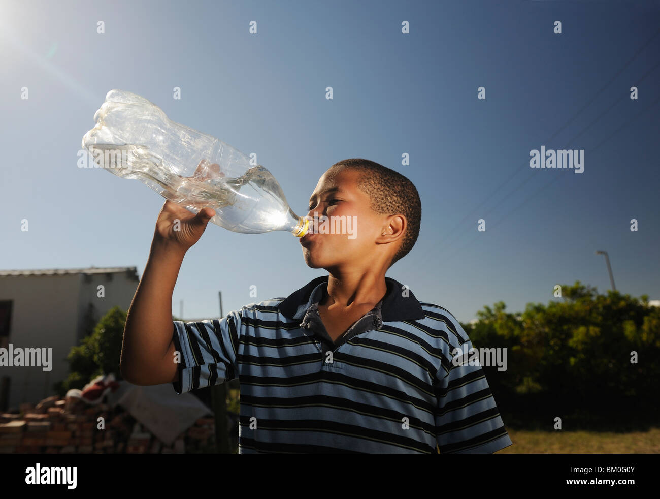 Boy (12-13) drinking water from plastic bottle, St Francis Bay, Sea Vista, Eastern Cape Province, South Africa - Stock Image