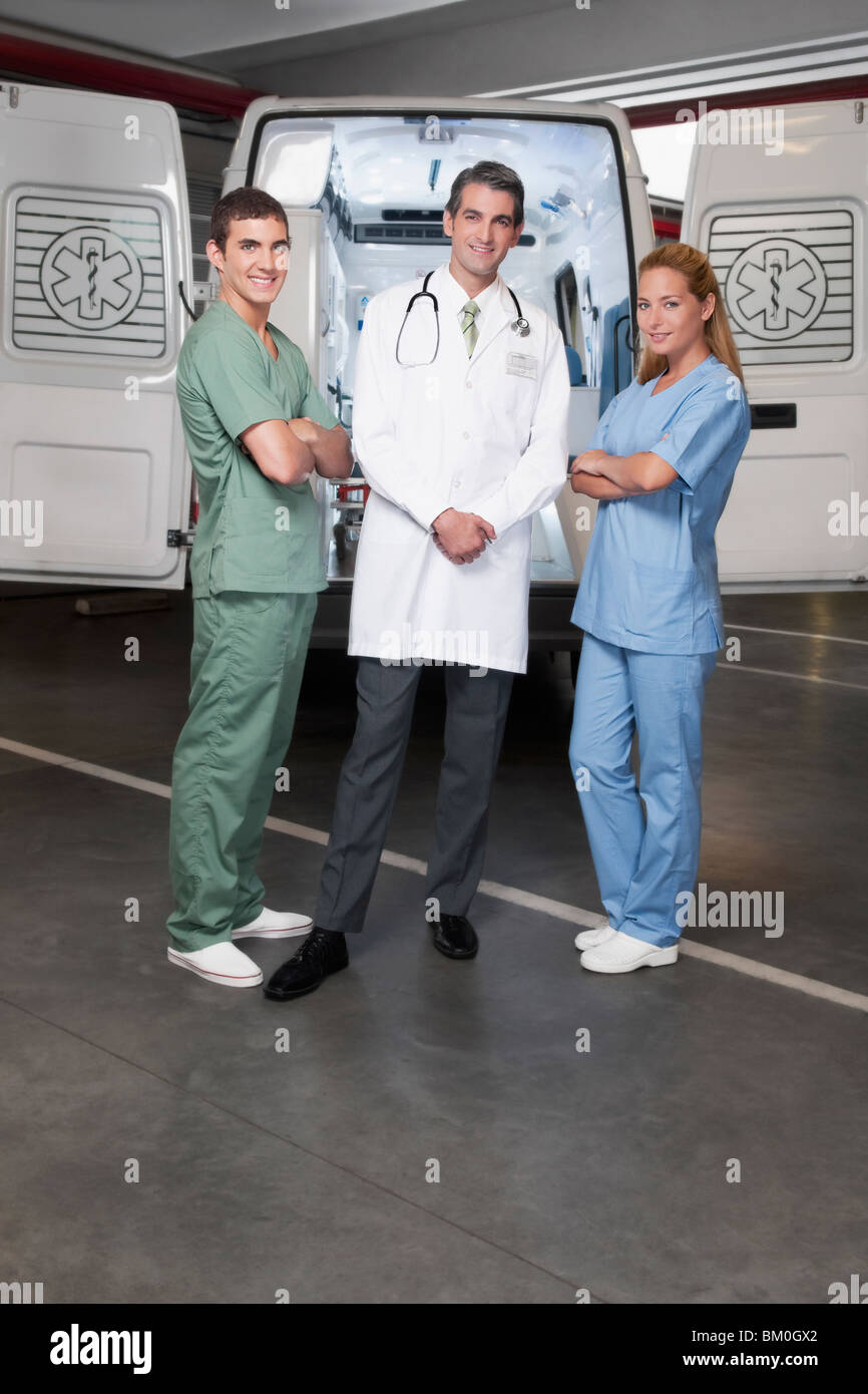 Doctor with co-workers standing in front of an ambulance - Stock Image