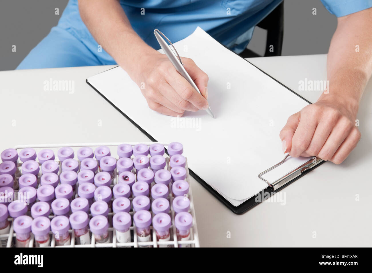 Female lab technician preparing a medical report - Stock Image