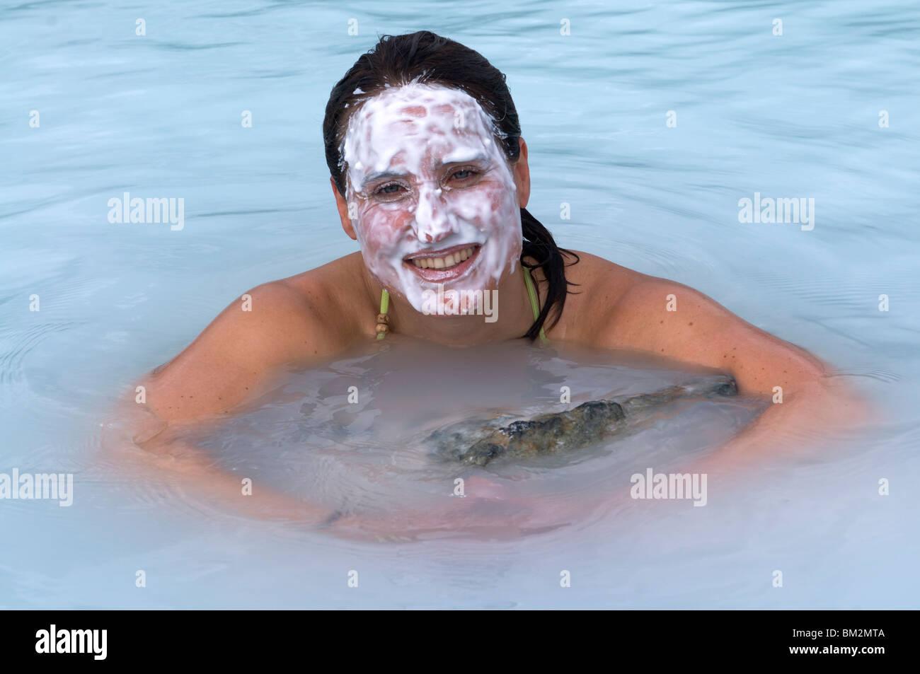 Young woman enjoying bathing in hot spring, Blue Lagoon, Iceland, Polar Regions - Stock Image