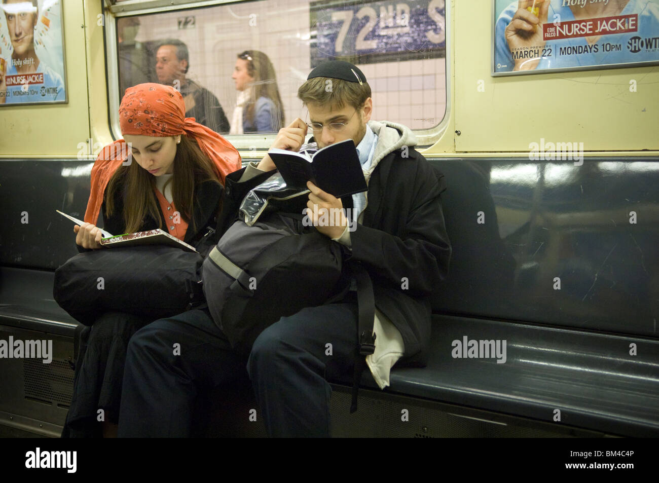 A couple reads on the subway in New York, on Sunday, May 9, 2010. (© Frances Roberts) - Stock Image
