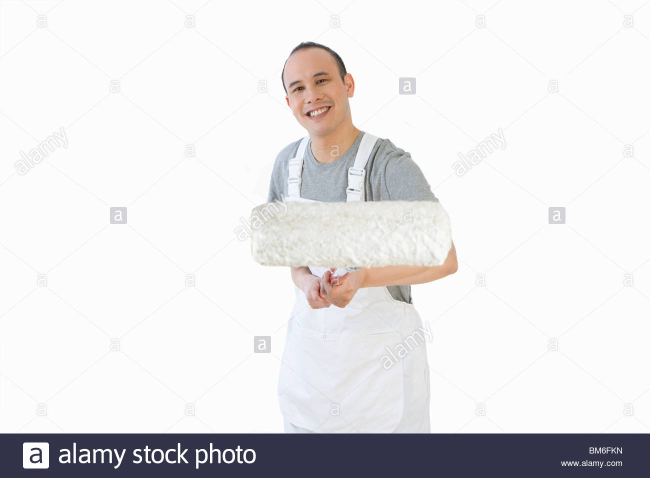 Smiling painter holding paint roller - Stock Image