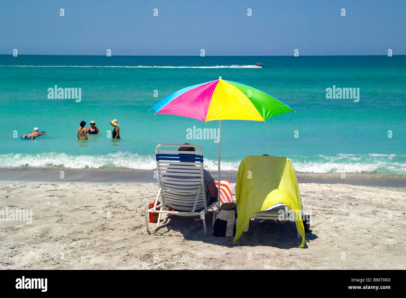Vacationers on shore watch their friends sunbathe in the warm Gulf of Mexico turquoise waters along the Longboat - Stock Image