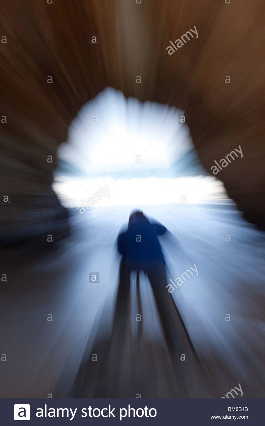 The shape of a photographer in a cave on the Californian coast - Stock Image