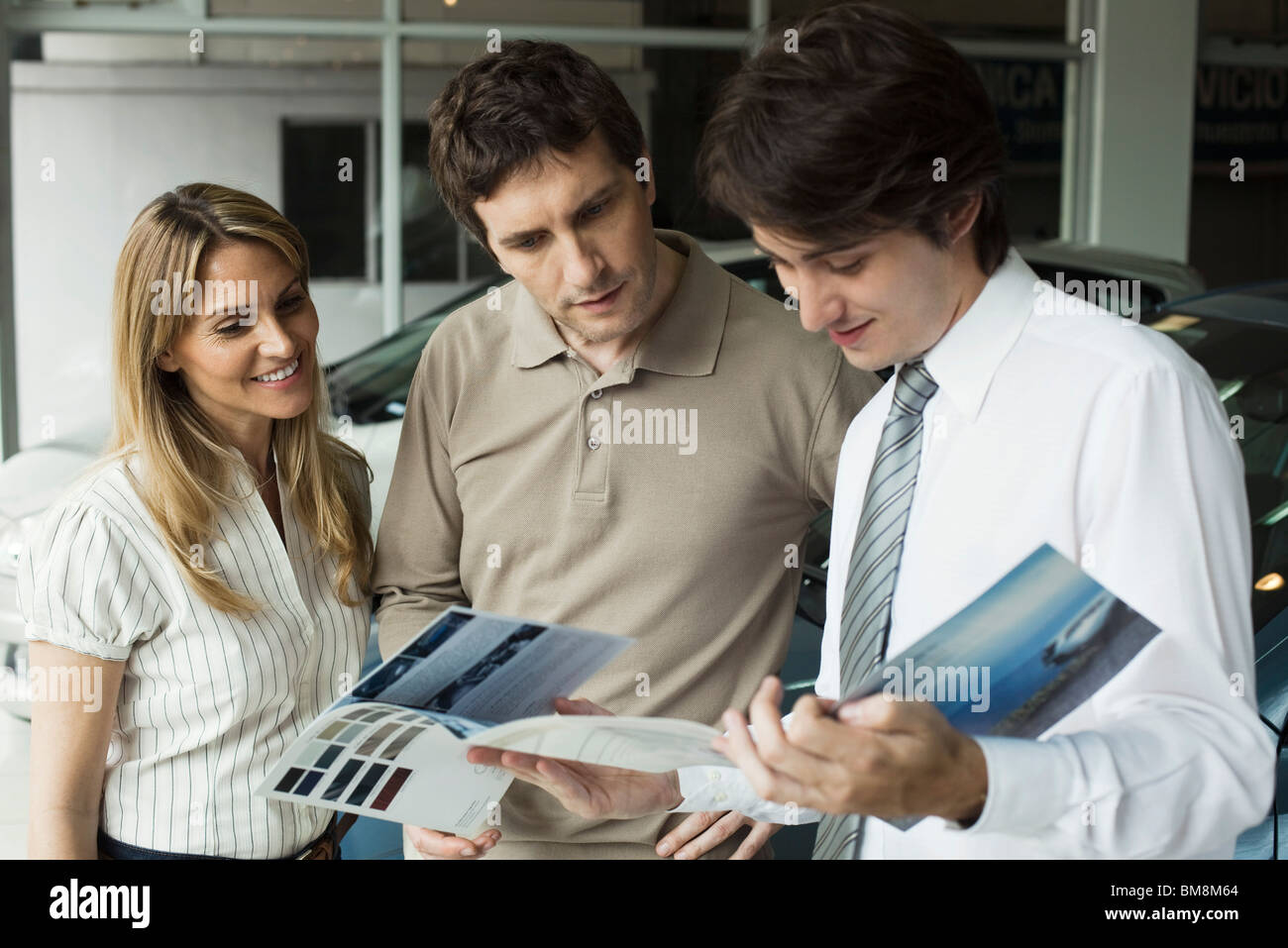 Car salesman showing couple brochure - Stock Image