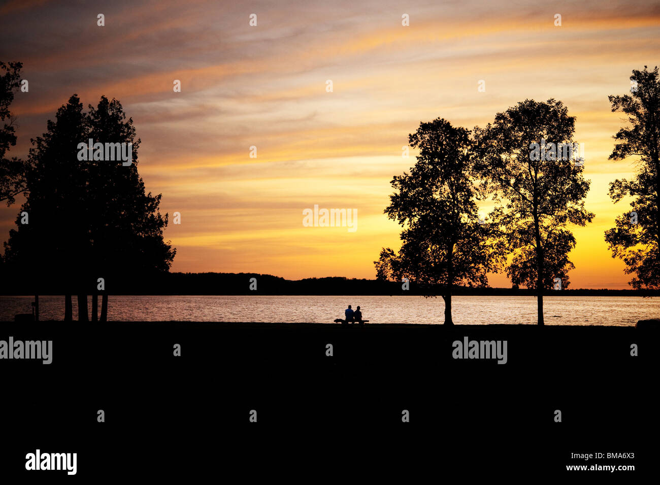 Elderly couple, silhouetted, sitting on a bench by lake at sunset - Stock Image