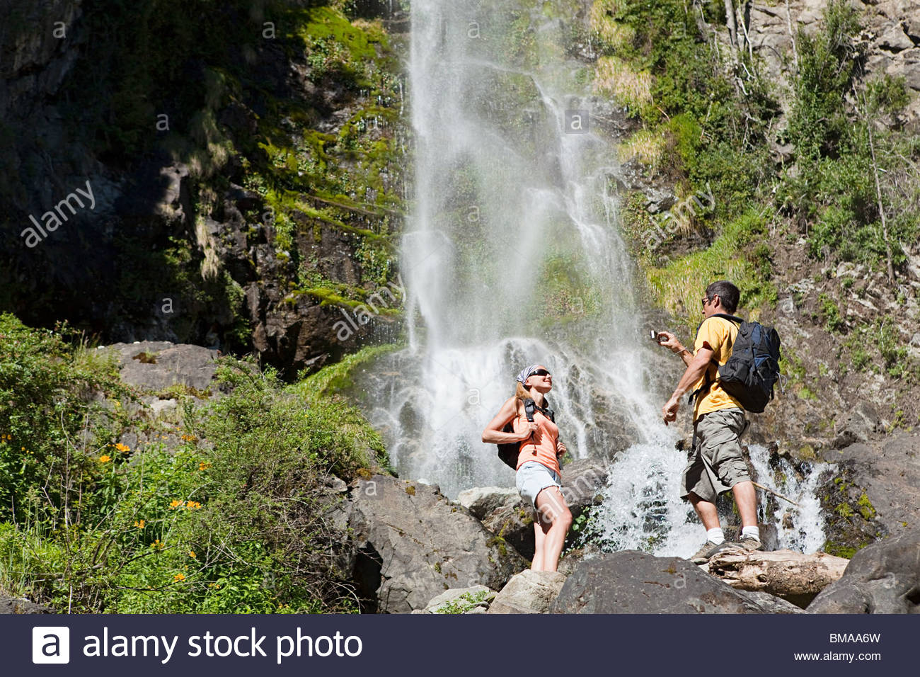 Couple taking pictures by waterfall - Stock Image