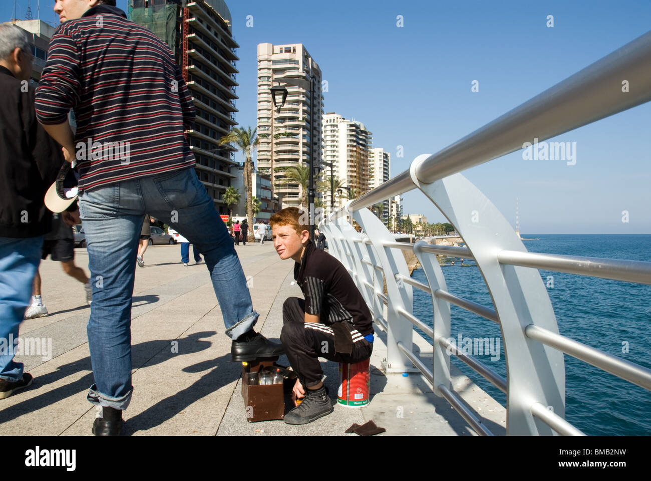 shoe cleaner boy do paint older man shoes at Beirut cornice Lebanon - Stock Image
