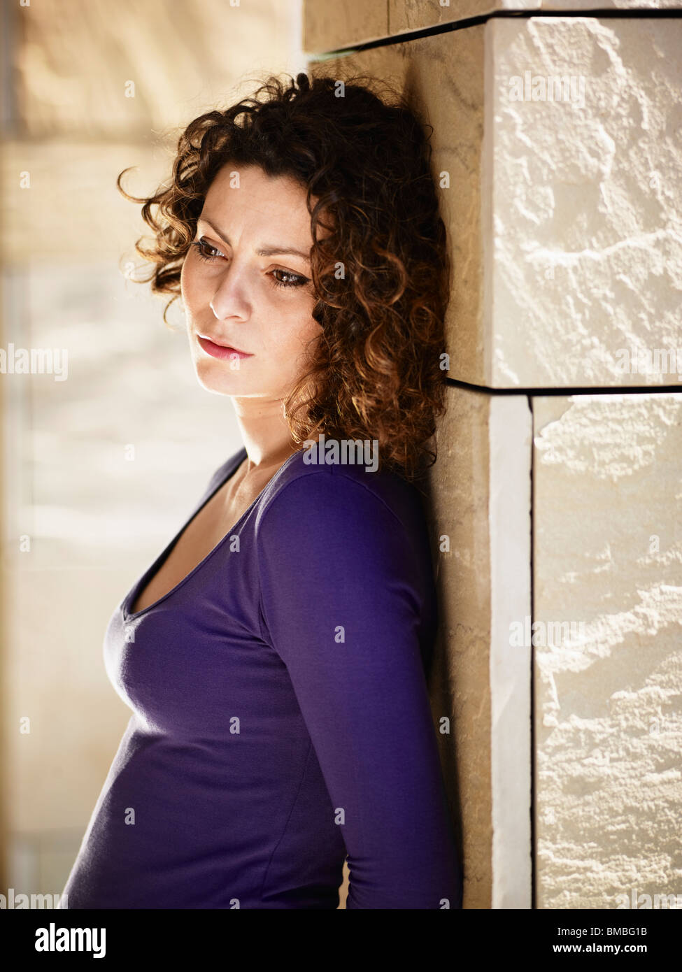 portrait of mid adult italian woman leaning on columns and crying - Stock Image