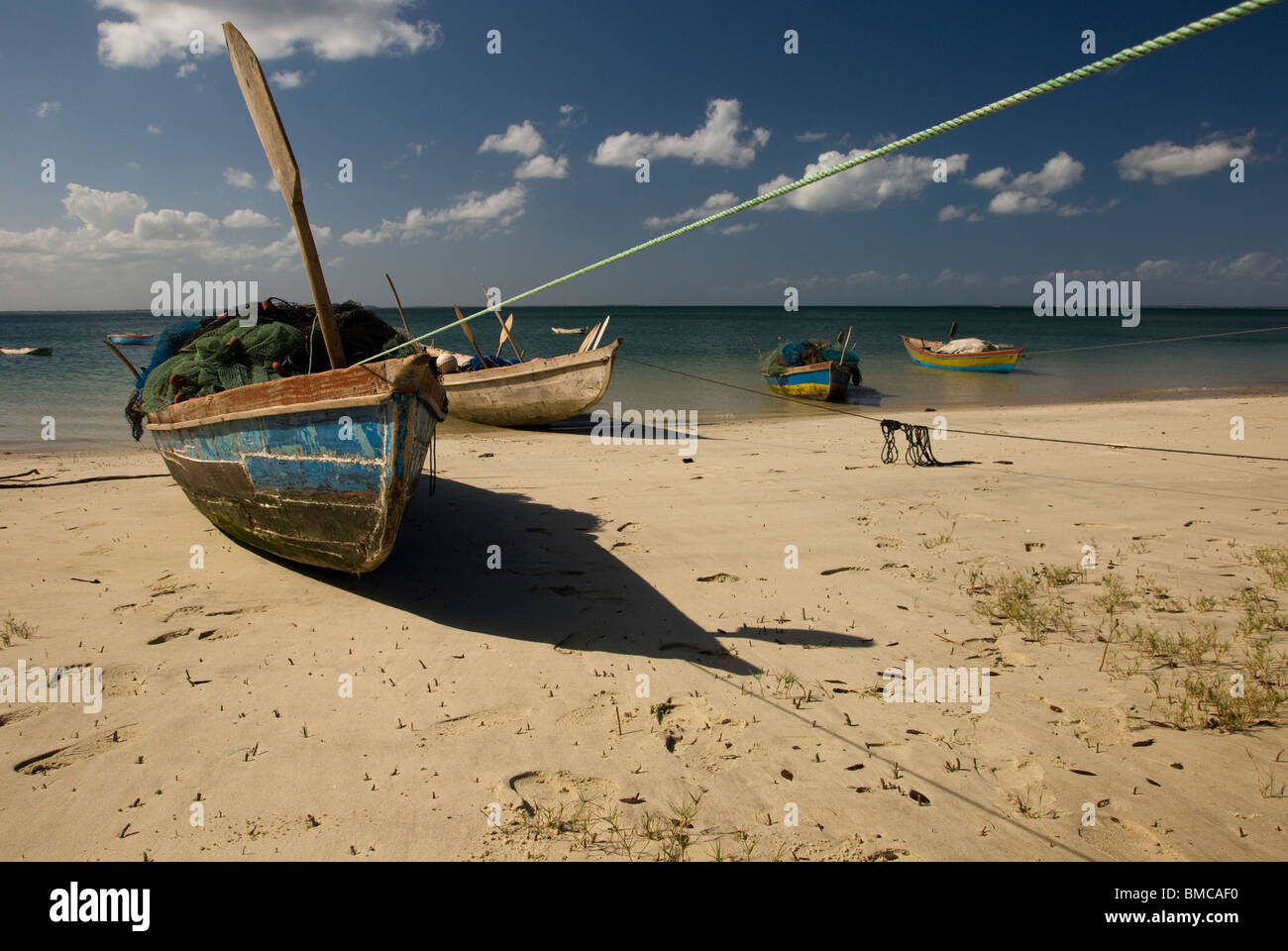 Fishing boats beached for an afternoon rest near Lunga, Nampula Province, Mozambique. - Stock Image
