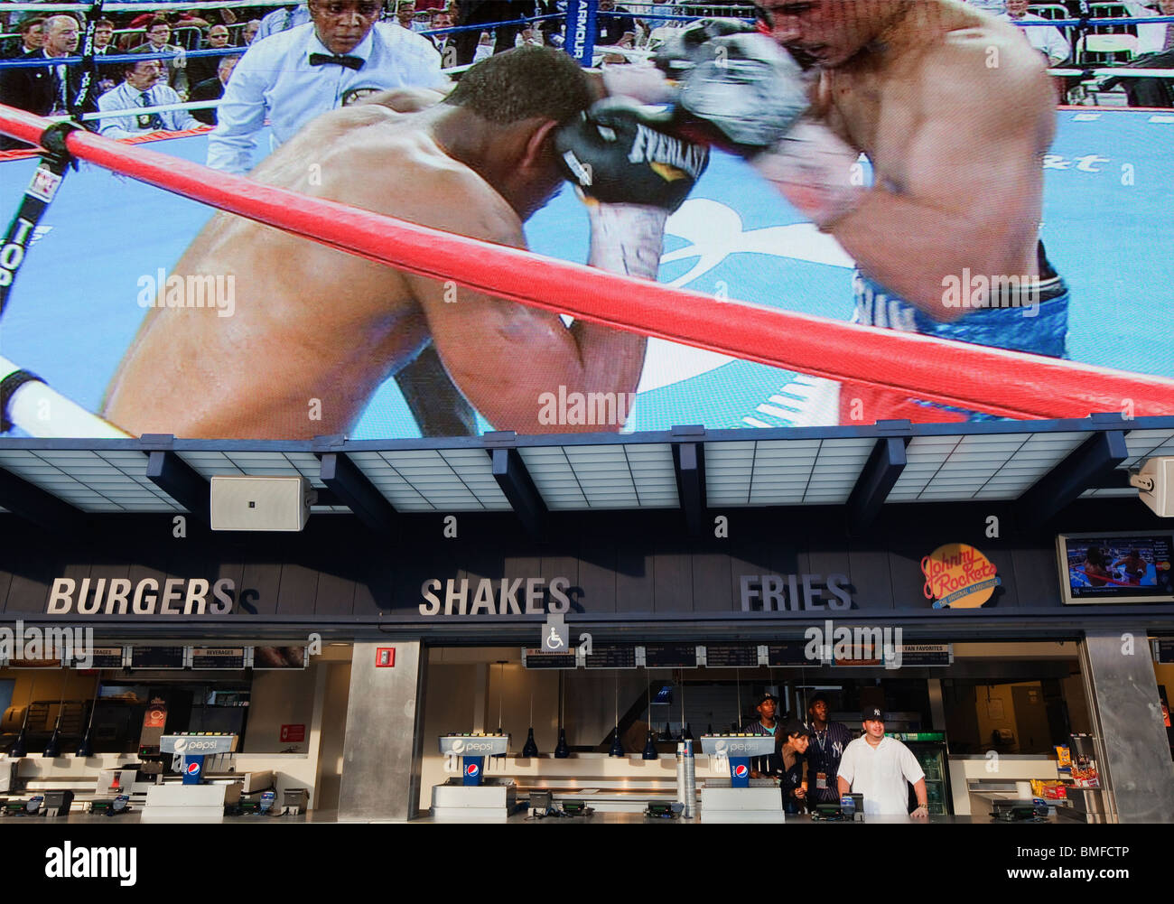 Yankee Stadium food stand workers look onto to a boxing match as the mega screen above them replays the action. - Stock Image