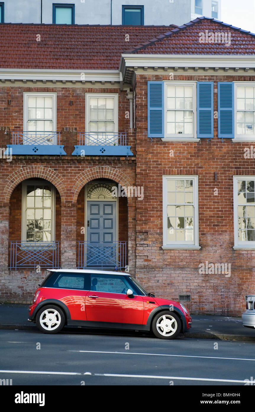 A red Mini Cooper in front a vintage brick house, Auckland, New Zealand - Stock Image