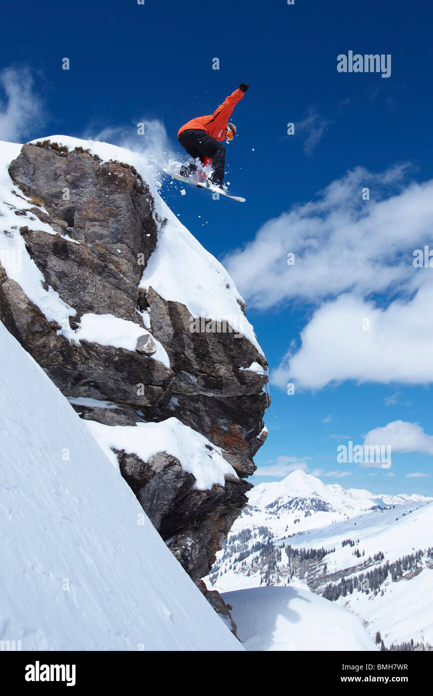 Male snowboarder jumping from cliff - Stock Image