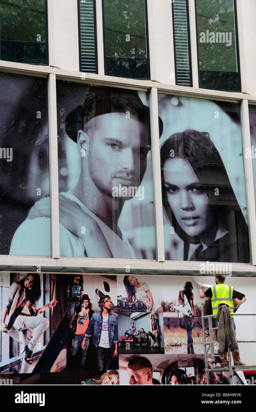 Man putting up posters billboards, Oxford Street, London, England, UK - Stock Image