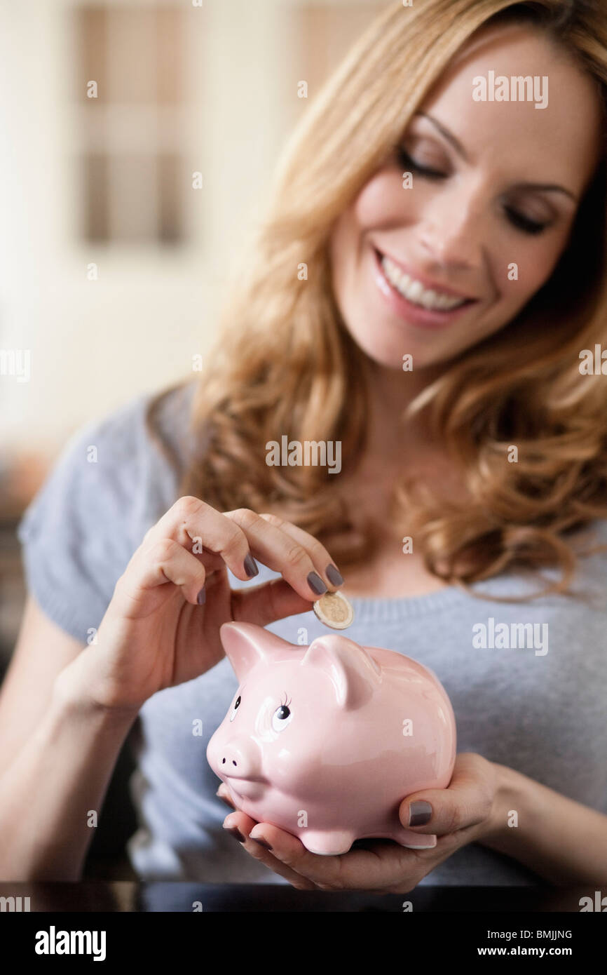 Woman saving money in piggy bank - Stock Image