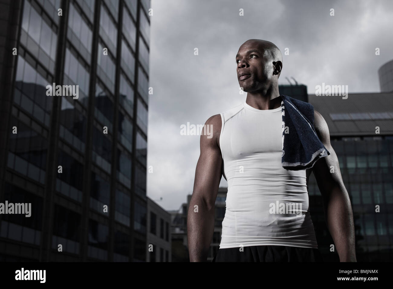 Fit man wearing sportswear backgrounded by modern city buildings - Stock Image
