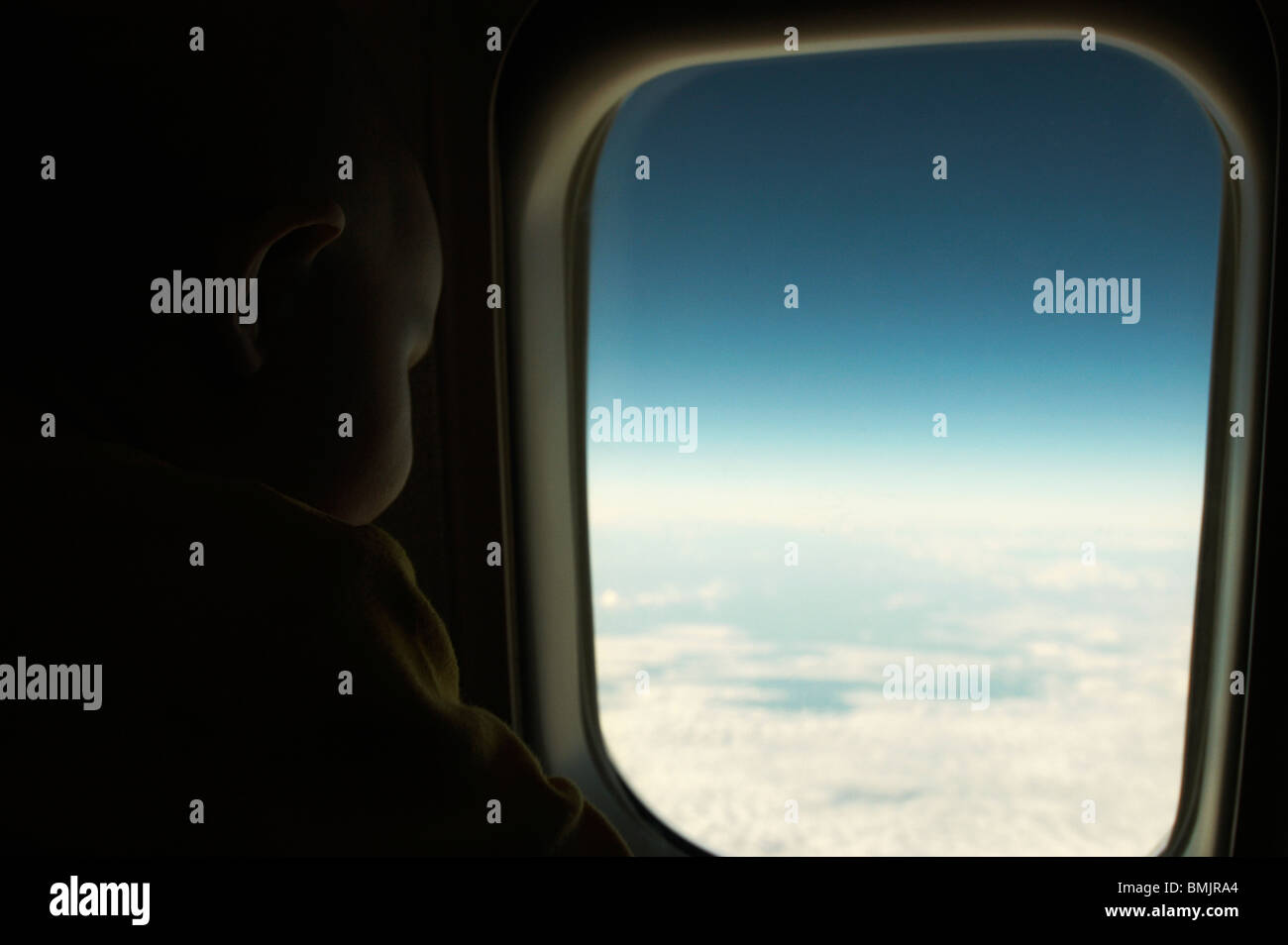 A baby looking out of a window in a plane - Stock Image
