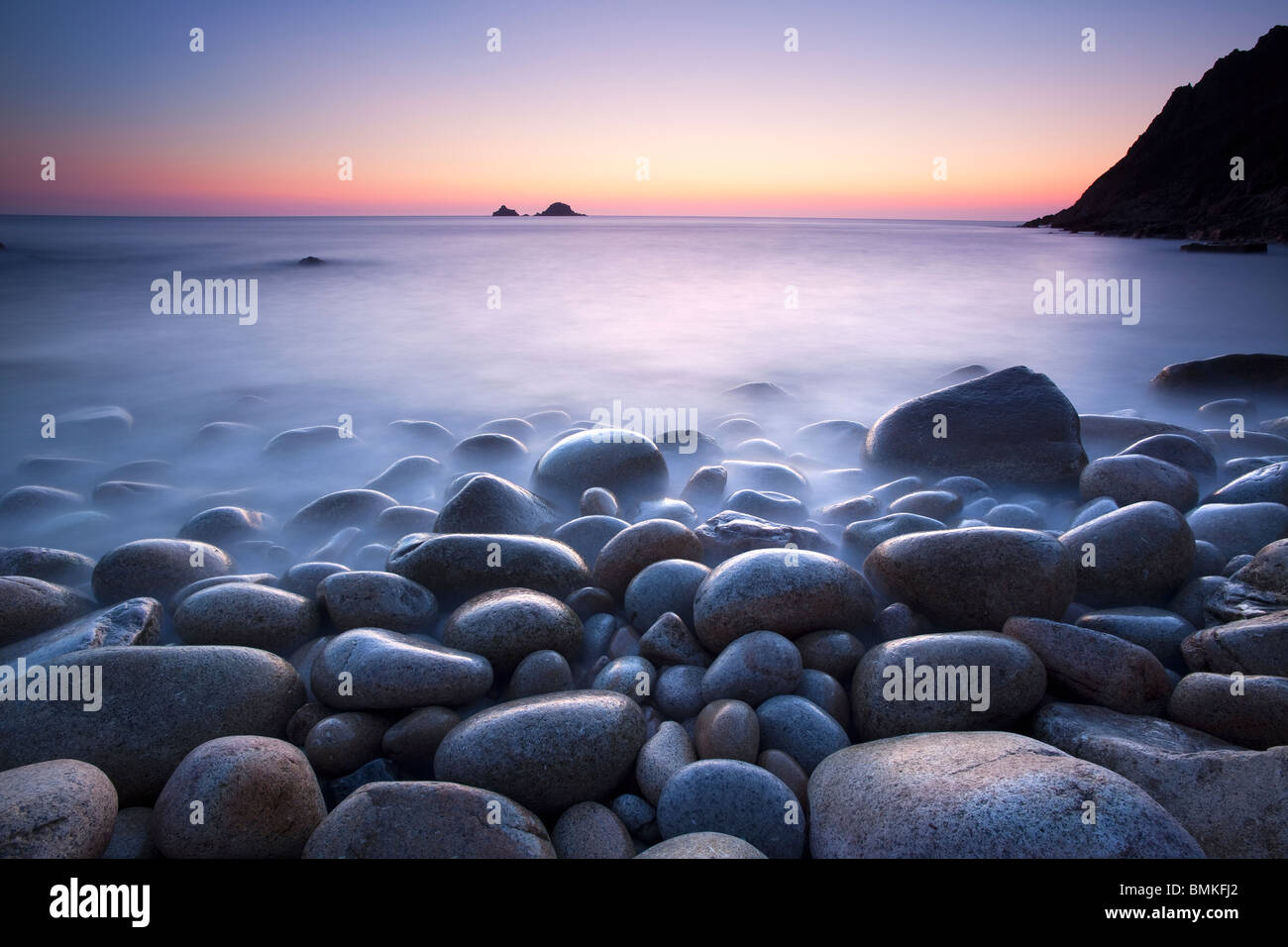 Boulders on beach at sunset Cornwall - Stock Image