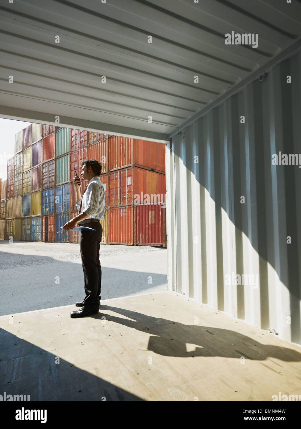 portrait of mid adult businessman standing near cargo container and talking . Vertical shape, side view, copy space - Stock Image