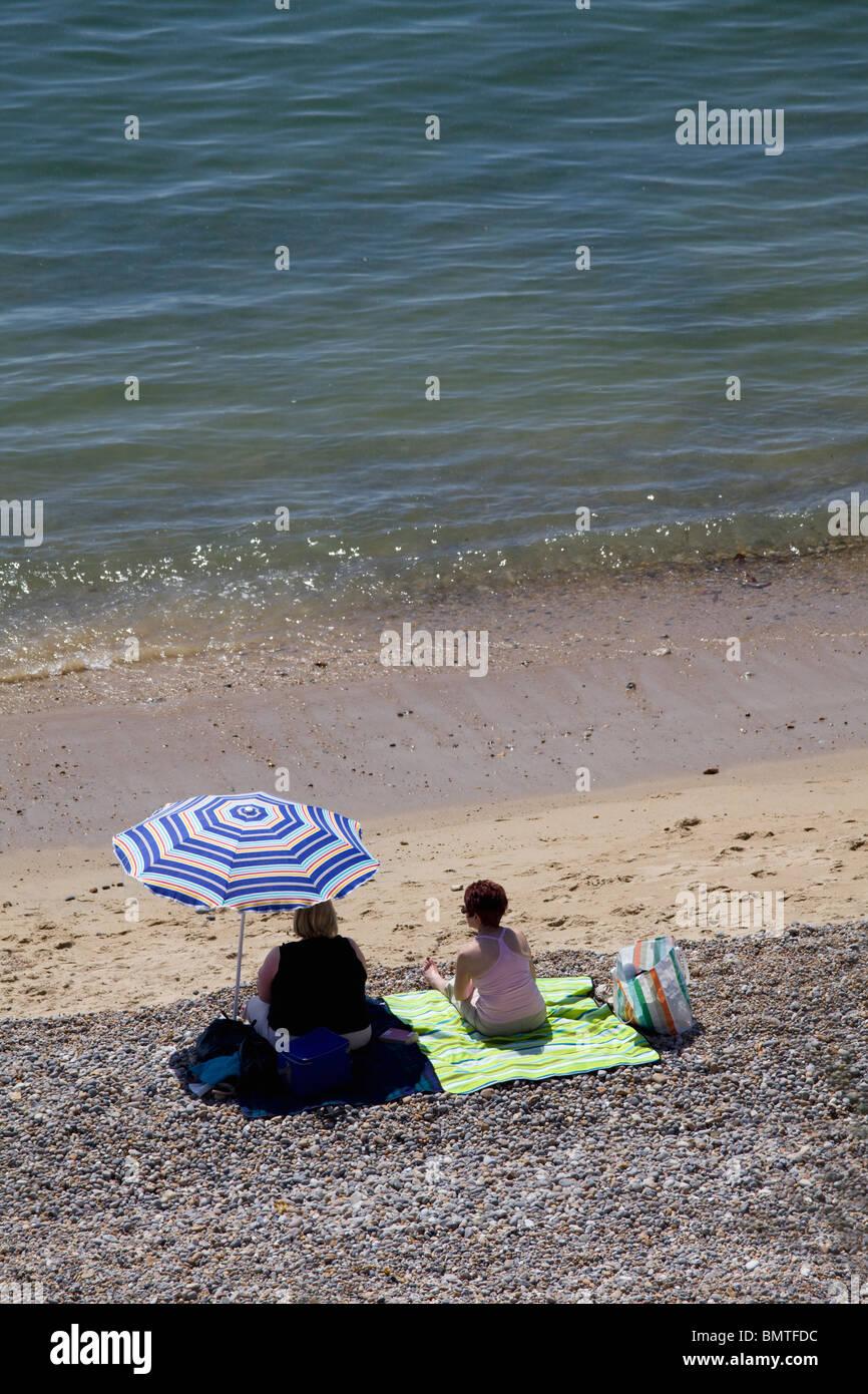 two-women-sitting-on-the-beach-with-a-parasol-seaton-devon-BMTFDC.jpg