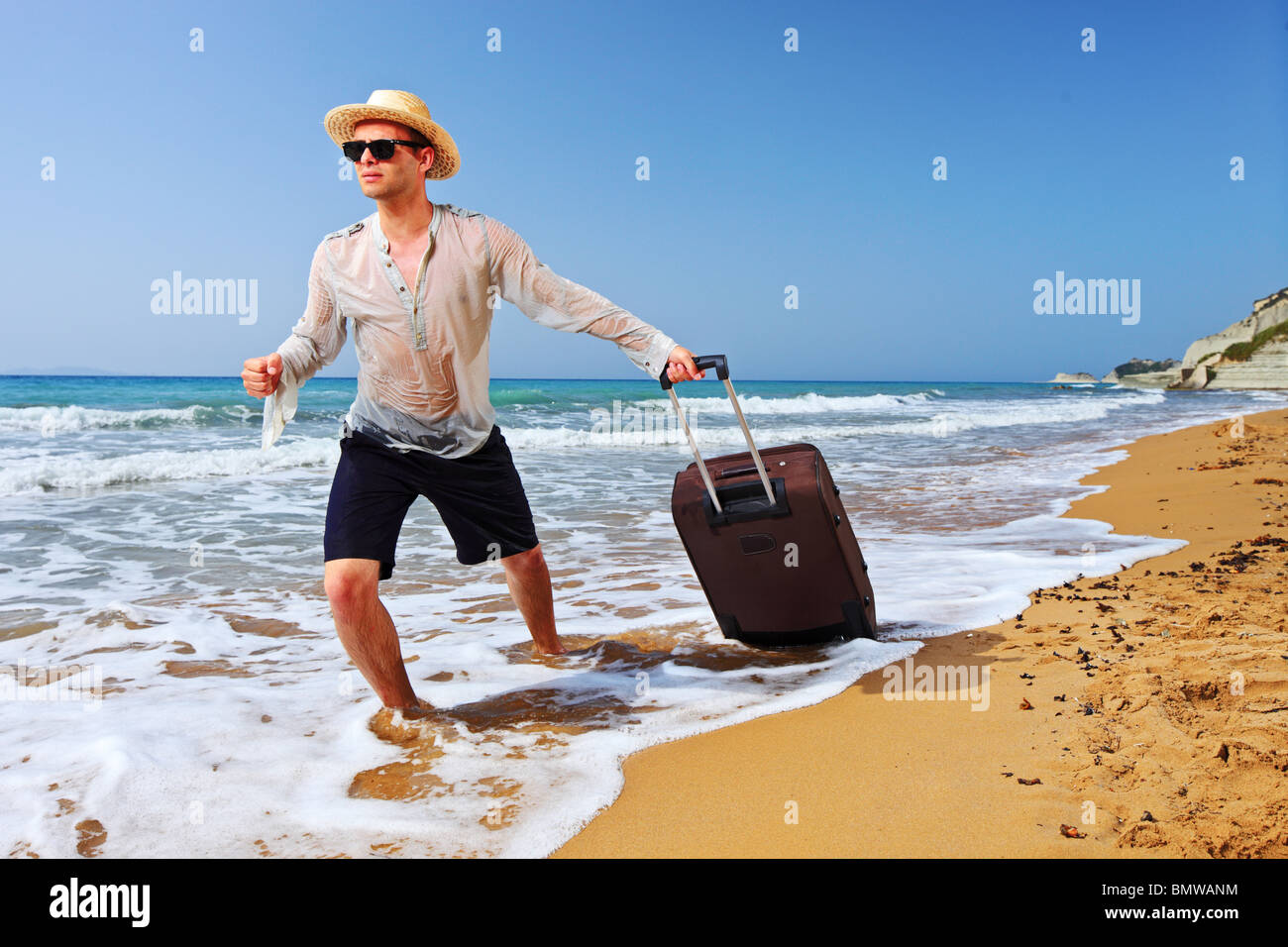 A tourist carrying a suitcase at the beach Peroulades at Corfu island, Greece Stock Photo