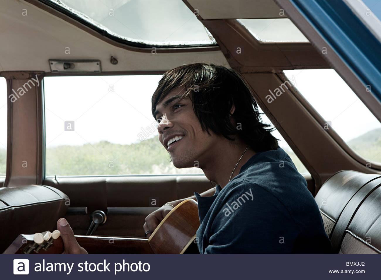 Young man inside car playing guitar - Stock Image