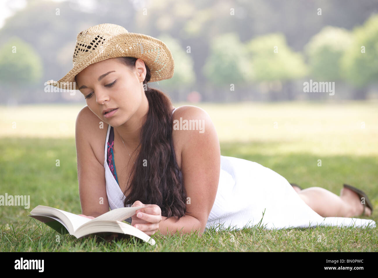 young attractive girl lying on grass while reading a book - Stock Image