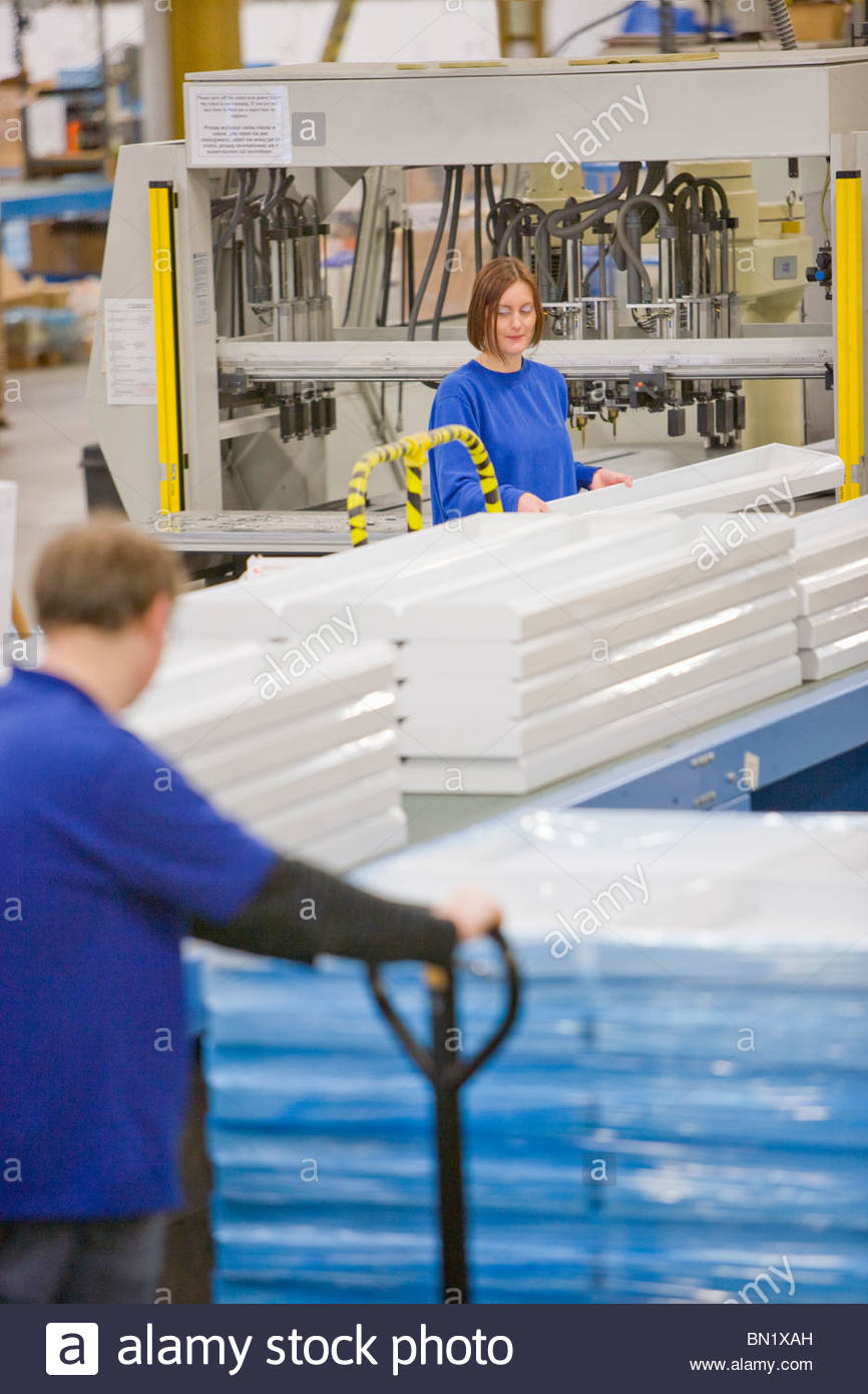 Workers processing and inspecting aluminium light fittings on production line in factory - Stock Image