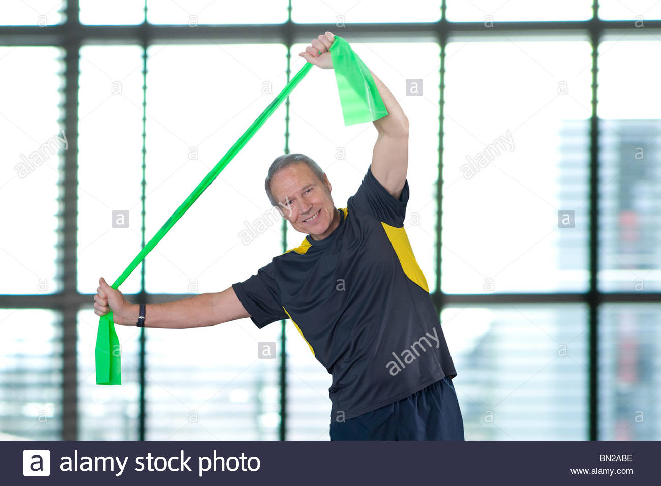 Portrait of smiling man stretching with resistance band overhead - Stock Image