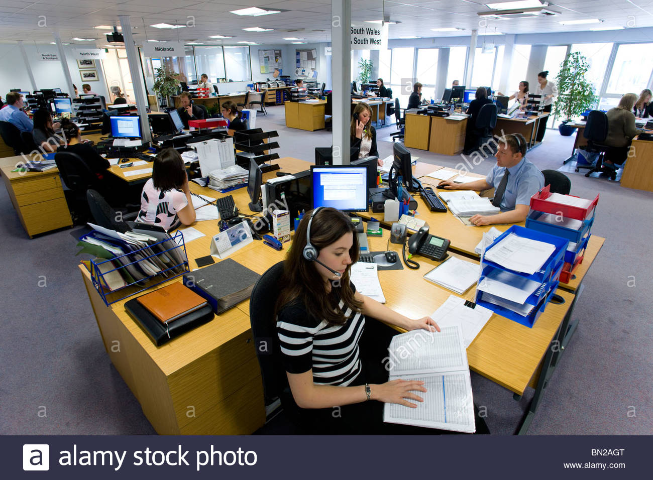 Sales people working at desks in call center office - Stock Image